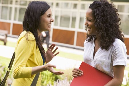 Two students standing outdoors talking Stock Photo - 3201155