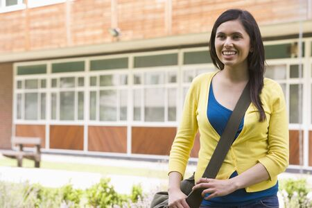 frontal views: Student standing outdoors smiling Stock Photo