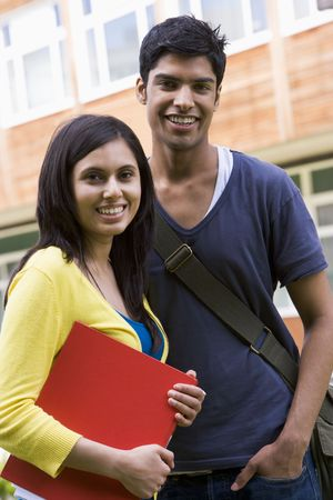Two students standing outdoors smiling photo