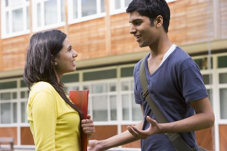 conversing: Two students standing outdoors smiling and talking Stock Photo