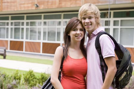 Two students standing outdoors with arms around waists smiling Stock Photo - 3201536