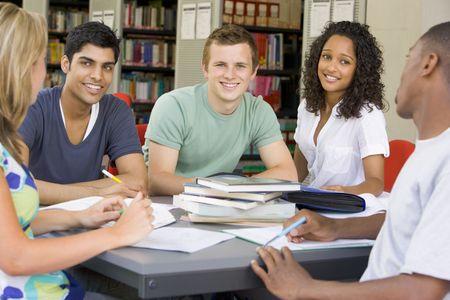 african student: Cinque persone che studiano in biblioteca (attenzione selettiva)