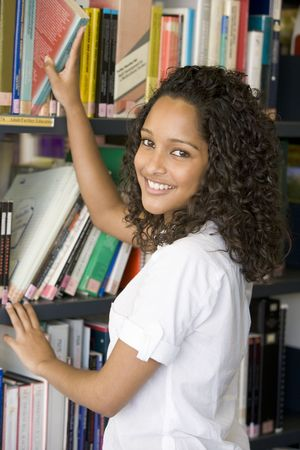 Woman in library pulling book off shelf Stock Photo - 3200665