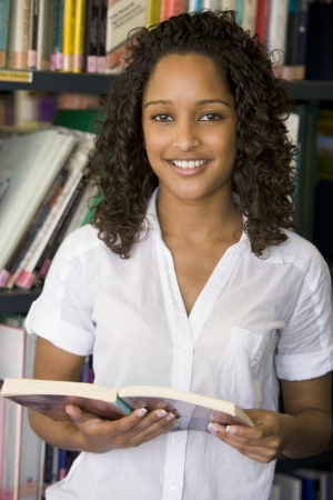 Woman in library holding book photo