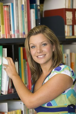 facing on the camera: Woman in library pulling book off shelf Stock Photo
