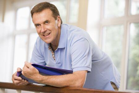 Teacher in corridor leaning on railing photo