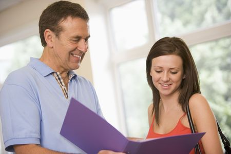 mature student: Teacher in corridor talking to student with notebooks Stock Photo