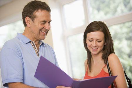 male teachers: Teacher in corridor talking to student with notebooks Stock Photo