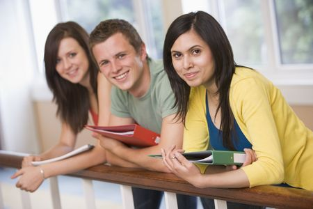 further: Three students in corridor leaning on railing (depth of field) Stock Photo