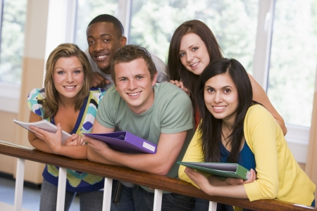 Five students in corridor leaning on railing with notebooks Stock Photo - 3205121