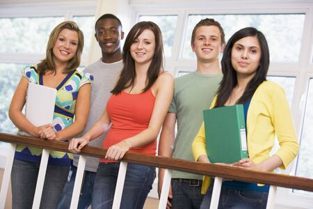 Five students in corridor leaning on railing with notebooks Stock Photo - 3200043