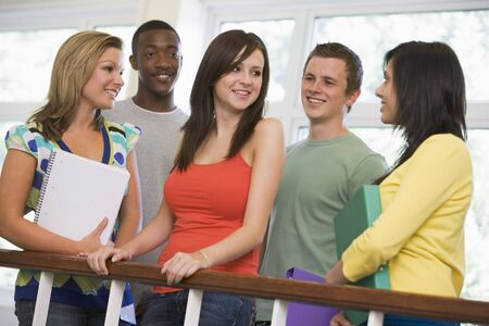 Five students in corridor leaning on railing with notebooks Stock Photo - 3204878