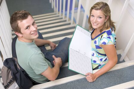 ruck sacks: Two students sitting on staircase with notebooks (selective focus)
