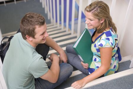 Two students sitting on staircase with notebooks (selective focus) photo