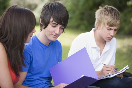 schoolwork: Three students outdoors studying (selective focus)