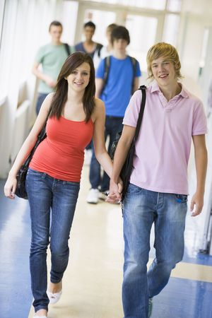 Two students walking in corridor holding hands with students in background (selective focus) photo