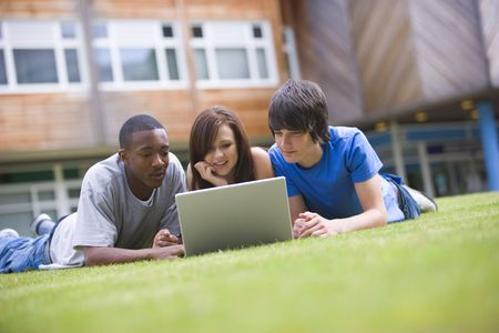 uses computer: Three students lying outdoors on lawn with laptop Stock Photo