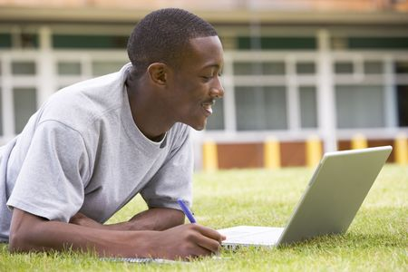 only one teenage boy: Student lying outdoors on lawn with laptop Stock Photo