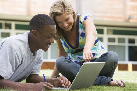 Two students outdoors on lawn with laptop photo
