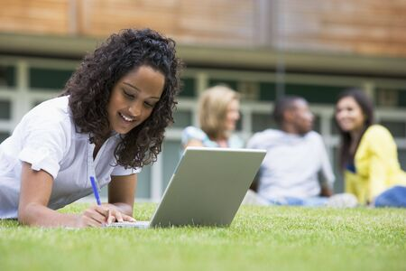 Student outdoors on lawn using laptop with other students in background (selective focus) Stock Photo - 3199386