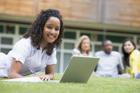 uses computer: Student outdoors on lawn using laptop with other students in background (selective focus) Stock Photo