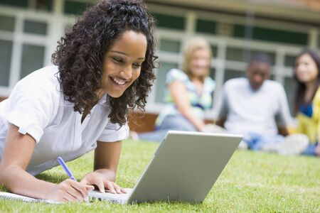 Student outdoors on lawn using laptop with other students in background (selective focus) Stock Photo - 3199543