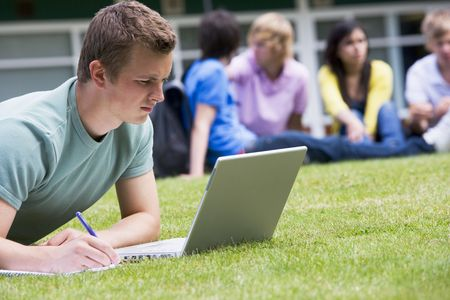 Student outdoors on lawn using laptop with other students in background (selective focus) Stock Photo - 3200742