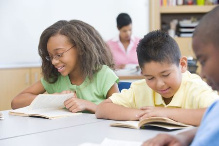 Students in class reading with teacher in background (selective focus) Stock Photo - 3199450