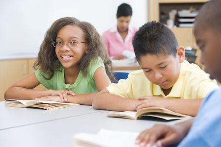 Los estudiantes en la clase de lectura con el maestro en el fondo (enfoque selectivo)