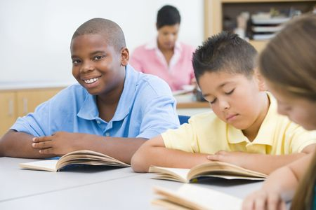 latin students: Students in class reading with teacher in background (selective focus)