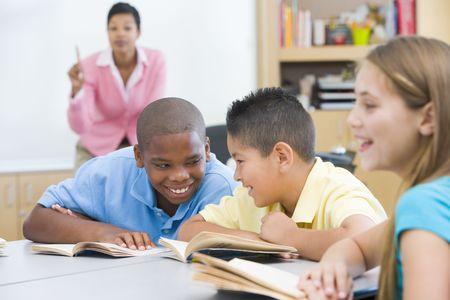sachant lire et �crire: Les �l�ves en classe de parler avec des enseignants en arri�re-plan (s�lective focus)  Banque d'images