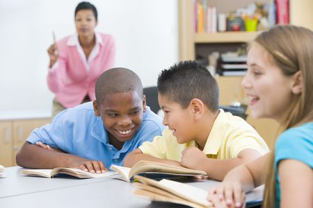 literacy instruction: Students in class talking with teacher in background (selective focus)