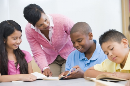 literacy instruction: Students in class reading with teacher helping (selective focus) Stock Photo