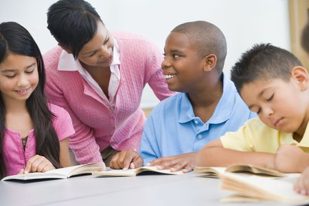 junior student: Students in class reading with teacher helping (selective focus) Stock Photo