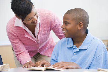 mentors: Student in class reading with teacher