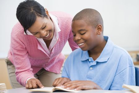 tween boy: Student in class reading with teacher