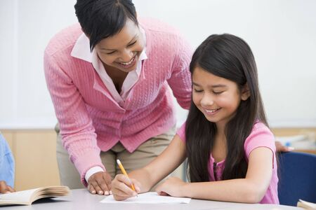 mentors: Student in class writing with teacher Stock Photo