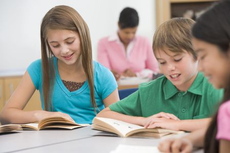 Students in class reading with teacher in background (selective focus) Stock Photo - 3204840