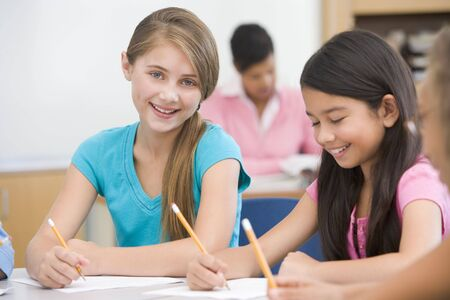 frontal portrait: Students in class writing with teacher in background (selective focus) Stock Photo