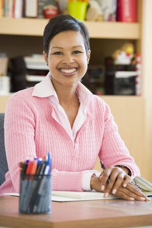 educadores: Maestro sentado en mesa de trabajo en clase (atenci�n selectiva)