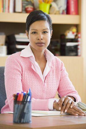 frontal portrait: Teacher sitting in class at desk (selective focus)