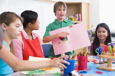 Student showing teacher and classmates his artwork (selective focus) photo
