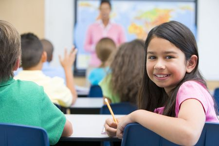 student studying: Student in class looking at camera with teacher in background (selective focus) Stock Photo
