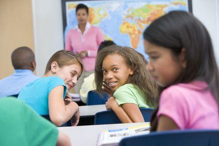 alumnos estudiando: Los estudiantes de estudiante bullying clase con el maestro en el fondo (enfoque selectivo)
