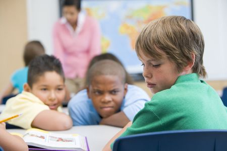 mentors: Student in class being bullied by students in background (selective focus) Stock Photo
