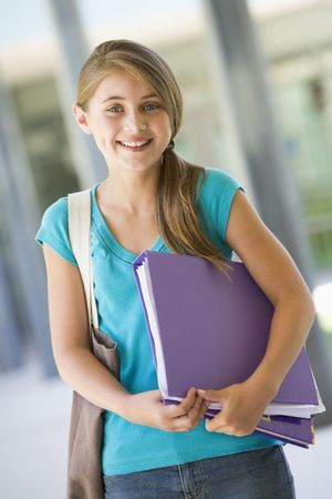 tweens: Student standing outside school with binder smiling (selective focus)