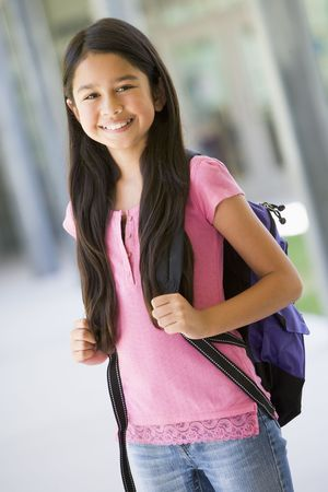 knap sack: Student standing outside school smiling (selective focus)