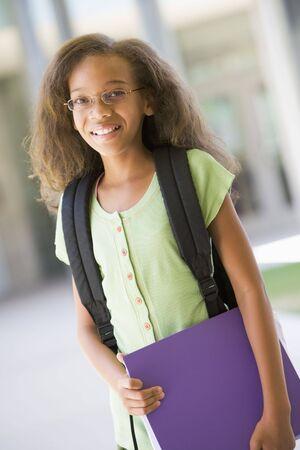 preadolescentes: Estudiante de pie fuera de la escuela celebraci�n de carpetas y sonriente (atenci�n selectiva)  Foto de archivo