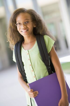 tweens: Student standing outside school holding binder and smiling (selective focus)