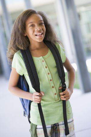 tweens: Student standing outside school smiling (selective focus)
